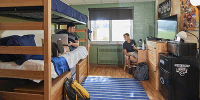 Student on bed with laptop speaking to student seated at desk