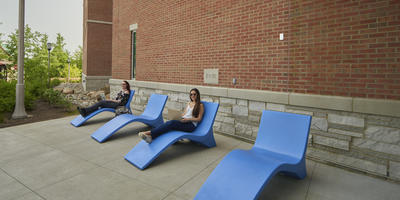 Two students on lounge chairs using laptops