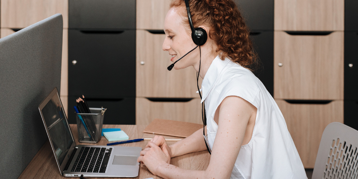 Woman with headset looking at a laptop